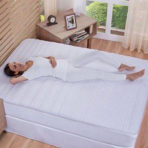 mujer durmiendo en una cama con cubre colchón