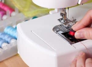 persona cambiando hilo de una máquina de coser