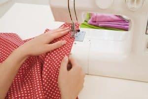 persona cosiendo con una máquina de coser blanca