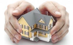 manos protegiendo una casa