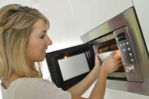 mujer poniendo un microondas