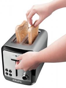 persona poniendo pan en una tostadora