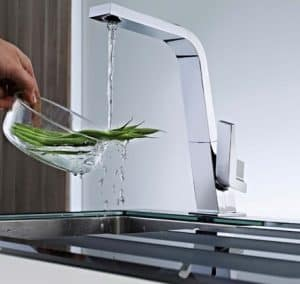 persona limpiando verdura con un grifo de cocina