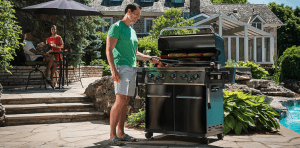 hombre cocinando en una barbacoa a gas