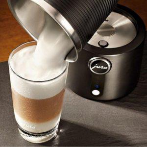 vaciando leche en un café desde un espumador de leche