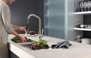 mujer usando un grifo de cocina