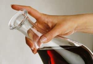 mano con un decantador de vino