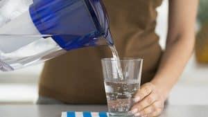 mujer llenando un vaso de una jarra de agua con filtro
