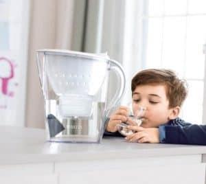 niño bebiendo agua de una jarra de agua con filtro