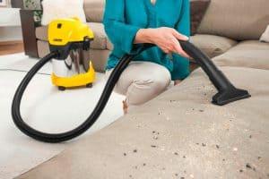 mujer limpiando el sofá con una aspiradora de tambor