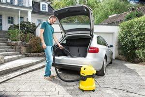persona limpiando el coche con una aspiradora de tambor