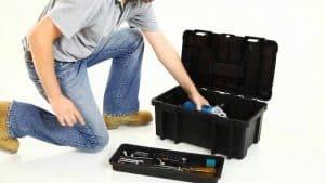 hombre cogiendo algo de una caja de herramientas