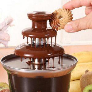 persona mojando una galleta en una fuente de chocolate