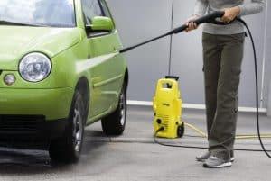 persona limpiando un coche con un limpiador de alta presión