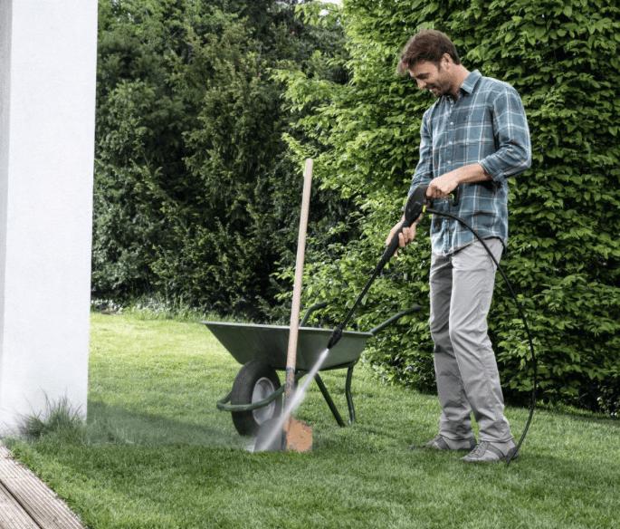 hombre limpiando una pala con un limpiador de alta presión
