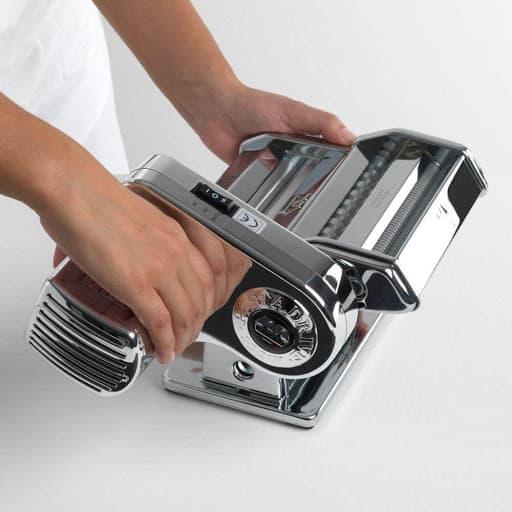 persona manipulando una máquina para hacer pasta