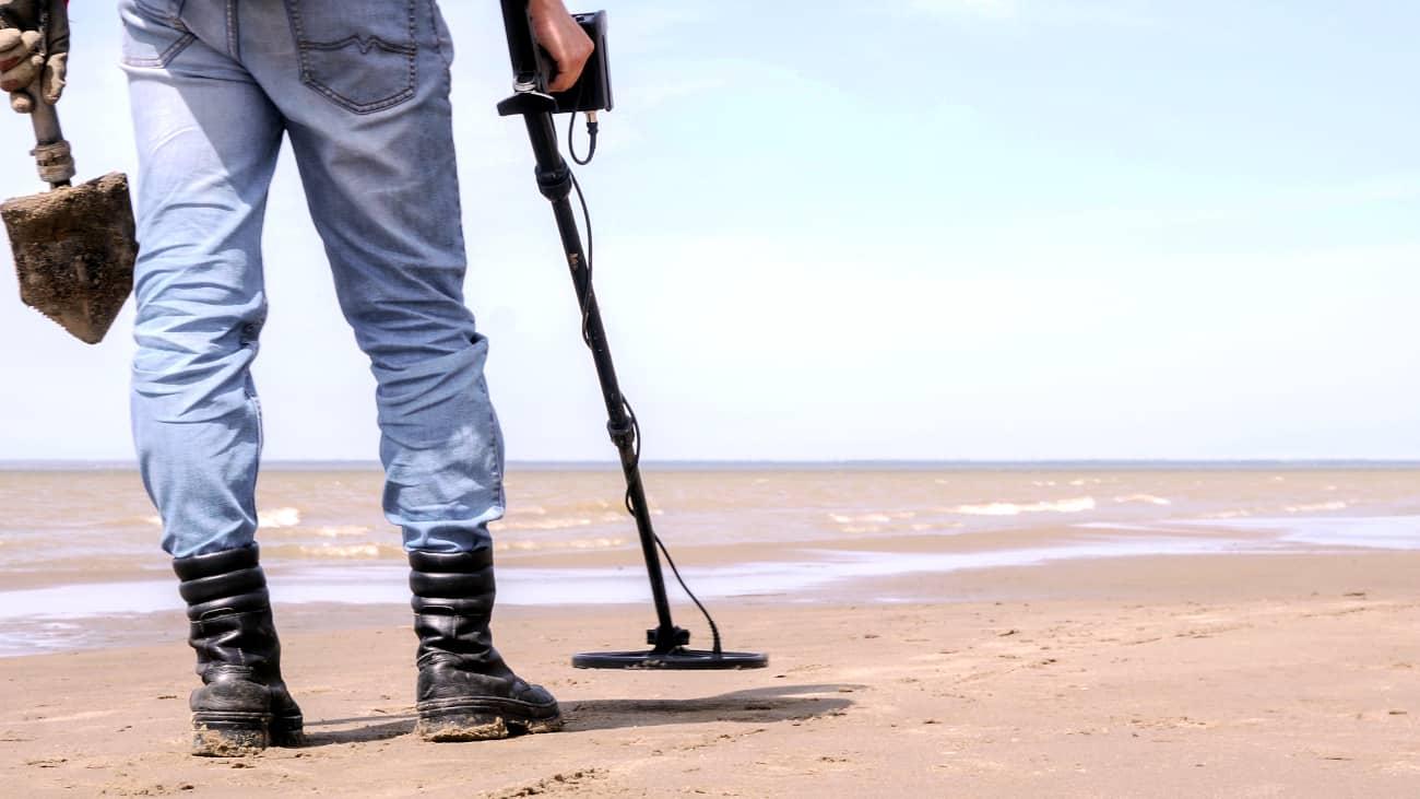 hombre usando un detector de metales en la playa