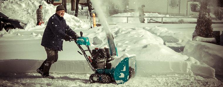 señor usando un soplador de nieve