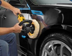 persona puliendo un coche con una pulidora de coche