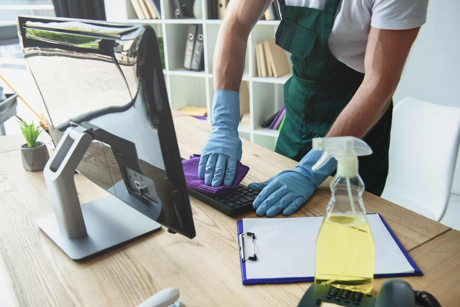 persona limpiando mesa de ordenador