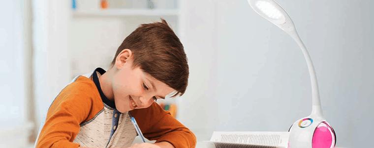 niño en una mesa con lámpara de oficina