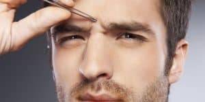 hombre usando pinzas de depilar