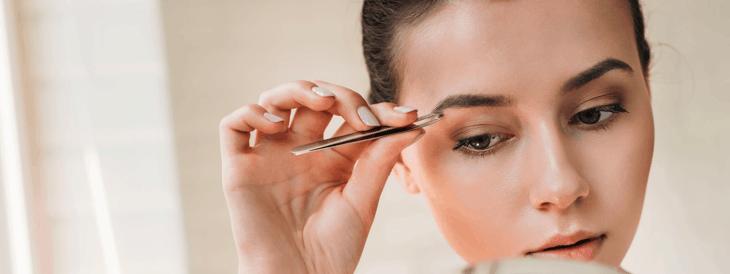 mujer usando pinzas de depilar