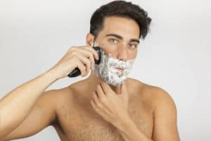 hombre afeitándose la barba con una afeitadora eléctrica