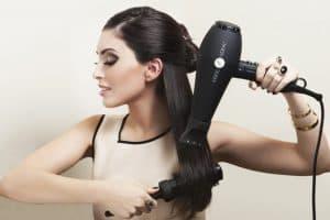 mujer secándose el pelo con un secador iónico negro