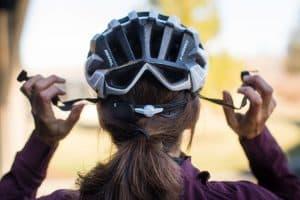 mujer poniéndose un casco de bicicleta