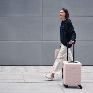 mujer con maleta rígida