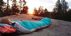 persona durmiendo en un saco de dormir