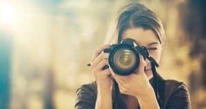 mujer usando una cámara de fotos réflex