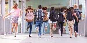niños con mochilas corriendo