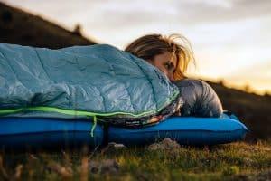 mujer en un saco de dormir sobre una colchoneta