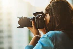mujer haciendo fotos con una cámara de fotos réflex