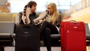 dos personas con dos maletas de mano
