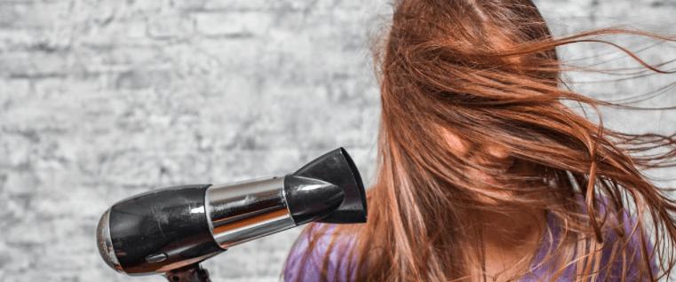 mujer con el pelo loco por un secador