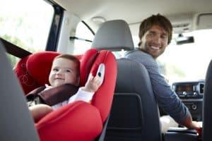 niño en una silla de coche para bebé roja