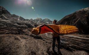 hombre con saco de dormir en la montaña