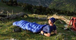 hombre en un saco de dormir en la montaña