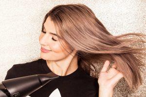 mujer secándose el pelo con un secador iónico