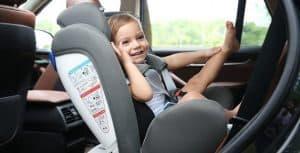 niño contento en una silla de coche para bebé