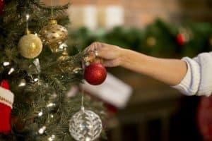persona poniendo bolas al árbol de Navidad