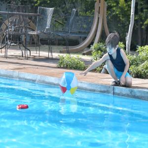 niño jugando en una piscina con alarma de piscina