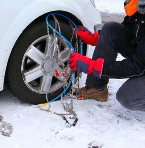 persona poniendo cadenas de nieve