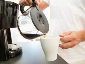 persona echando café de una cafetera de filtro