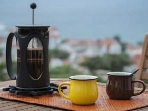 cafetera de pistón y tazas de café
