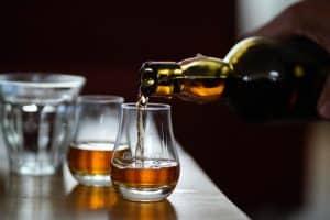 persona sirviendo whisky en vasos pequeños