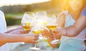 personas brindando con vino blanco